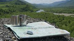 Travel accessories to the adventure in mountains: mug, conpass and map on the Stock Photos