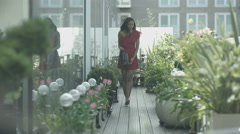 4K Attractive young woman watering plants in city rooftop garden Stock Footage