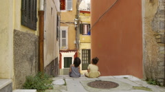 Children sit on the stairs of the narrow streets Stock Footage