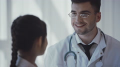 Pediatrician doctor examining little girl in a clinic - stock footage