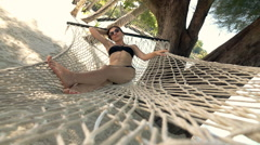 Young woman in bikini relaxing on hammock on beach, super slow motion 240fps Stock Footage