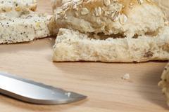 Oat flake bread rolls laying on a wodden breadboard Stock Photos