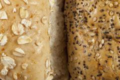 Two wholegrain seeded bread rolls side by side - stock photo