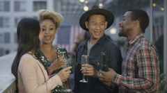 4K Portrait of happy smiling friends drinking & socializing on city rooftop Stock Footage