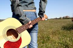 A woman holding a guitar looking at an empty field - stock photo
