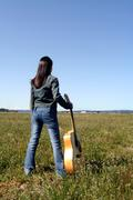 A woman holding a guitar looking at an empty field Stock Photos
