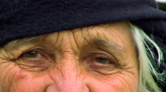 Eyes and wrinkles on the face of an old woman close up - stock footage