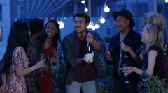 4K Man celebrating with friends on city rooftop shaking & spraying champagne Stock Footage