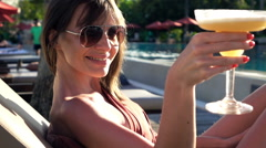 Portrait of happy, young woman raising toast to camera on sunbed, super slow mot Stock Footage