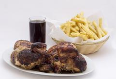 "Roasted chicken leg with fries potato called ""Pollo a la Brasa"" in South America - stock photo"