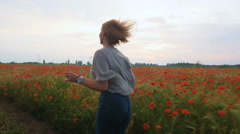 Happy young girl running in poppy field and having some fun - stock footage