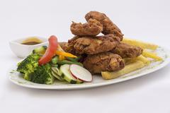 Plate of chicken wings and salad, served with passion fruit spicy garnish. Stock Photos