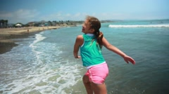 Slow motion of girl running on the ocean, looking back and smiling at camera - stock footage