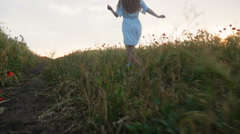 Young happy girl running in poppy field in white dress, slow motion Stock Footage