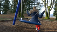 Girl swinging on a swing in the park Stock Footage