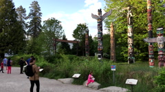 People taking picture in front of native totem poles inside Stanley Park Stock Footage