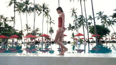 Sexy woman in swimsuit walking on edge of swimming pool, super slow motion 240fp Stock Footage