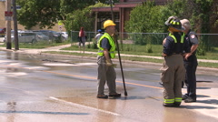 Police and firefighters at scene of city watermain break that buckled street Stock Footage