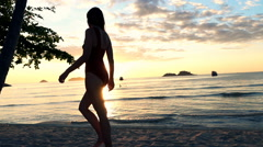 Sexy woman in swimsuit walking on beach during sunset, super slow motion 240fps Stock Footage