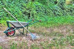hdr wheelbarrow garden rake tools spring - stock photo