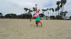 Cool slow motion of young girl doing gymnastics at the beach Stock Footage