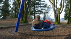 Girl relaxing on a swing in the park Stock Footage