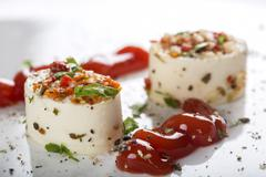 Appetizers with cheese and various ingredients and tomato sauce - stock photo