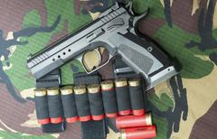 Firearm Pistol on military camouflage background Stock Photos