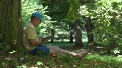 Man spent his holiday time reading novel book under old tree in park. 4K Stock Footage