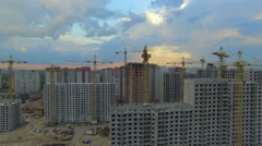 Aerial. Construction site with many cranes at a big city. Sunset time. - stock footage