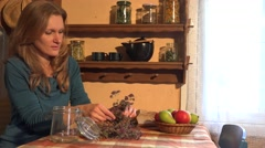 Herbalist girl put oregano in glass. Ancient rural room. 4K Stock Footage