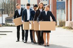 Group Of Unemployed Businesspeople With Cardboard Boxes Standing In A Line Stock Photos
