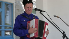 Man sings into a microphone and playing the accordion, Russian folk  Stock Footage