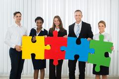 Group Of Businesspeople Holding Multi-colored Puzzle Pieces In Office Stock Photos