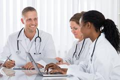 Group Of Happy Multi-racial Doctors With Laptop In Meeting Stock Photos