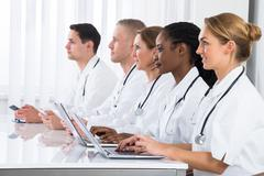 Group Of Multi-racial Doctors Using Laptop In Meeting Stock Photos
