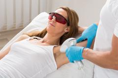 Mature Woman Receiving Underarm Laser Hair Removal Treatment - stock photo