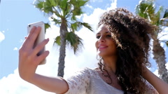 Young woman taking selfie with a smart phone against sky and palmes, slow motion Stock Footage