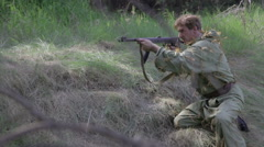 Soviet soldier fires back and drops the wounded. World war II. - stock footage