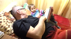 Parent reads book to his child Stock Footage