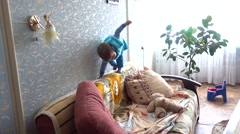 Mischief child fails to climbs on back of sofa Stock Footage