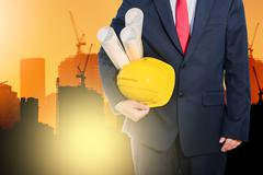engineer holding yellow helmet for workers security on background of new high - stock photo