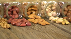 Mix of nuts in the glass jars , on the table. Stock Footage