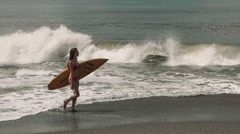 Young woman walking with a surf board in front of big waves Stock Footage