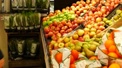 Woman in the supermarket coming up to the fruit counter. She choosing apples Stock Footage