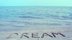 Inscription Dream on sea beach sand, with the wave. Stock Footage