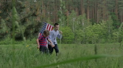 Two boys running in the forest with US flag - stock footage