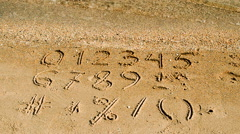 Digits & signs written on a beach sand Stock Footage