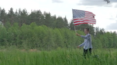 Happy boy with American flag running Stock Footage