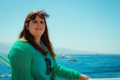 Profile view of one smiling woman looking away at sea - stock photo